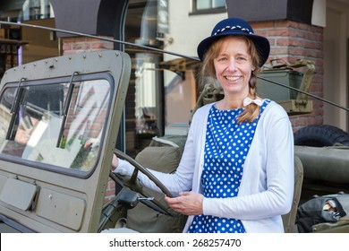 European middle aged woman steering green military jeep on liberation party. The caucasian woman wears a blue dress and a hat. She's looking at the camera
