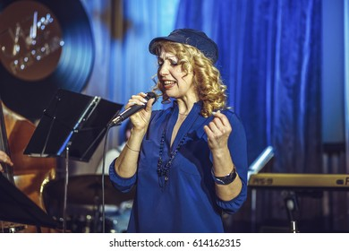 A European middle-aged female singer in a cap sings into the microphone on the restaurant scene.