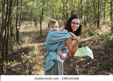 European mother babywearing one year old on a hike in the forest.