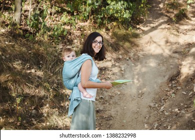 European mother babywearing one year old on a hike in the forest, holding a map.