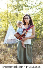 European mother babywearing one-year-old baby in a rainbow striped sling, standing by a wigwam tent in a garden.