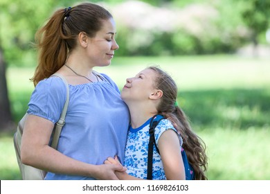 European mother and child looking each other and smiling together, summer park