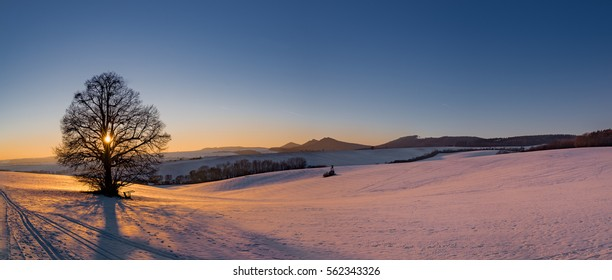 European mountains Chriby near city Uherske Hradiste with a Buchlov castle in the background. Sunset making beautiful colors on frozen fields