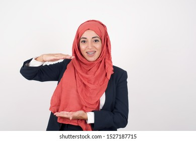 European Muslim woman over isolated background gesturing with hands showing big and large size sign, measure symbol. Smiling looking at the camera. Measuring concept.