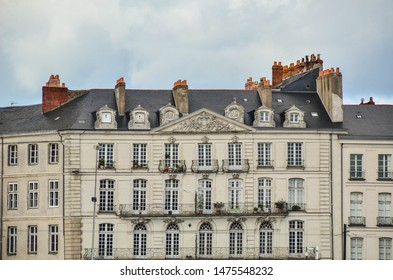 European old typical building with elegant windows, balconies and pipes in baroque style. Nantes, France