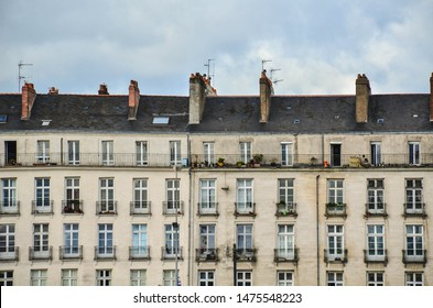 European old typical building with windows, balconies and pipes. Patterned photo for background. Nantes, France