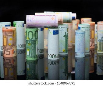 European paper money in rolls on black background with reflection. Business and financial concept with euro banknotes.