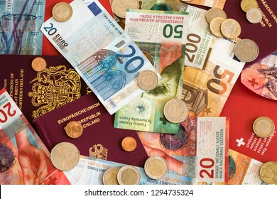 European passports and Swiss franc and Euro coins and bills mixed close up background