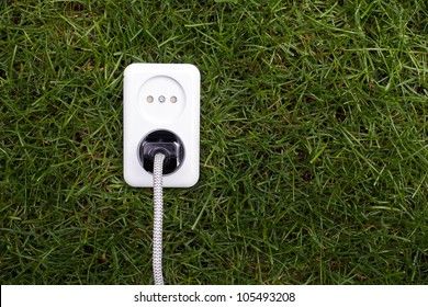 European power socket and plug on grass. Energy concept