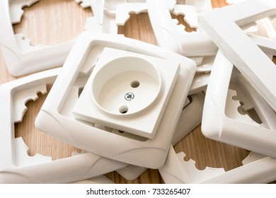 European power socket and the stack of socket frames on the light wooden table.