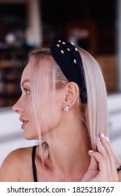 European pretty woman in stylish headband wearing beautiful earings