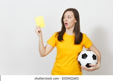 European serious severe young woman, football referee or player in yellow uniform showing yellow card, holding soccer ball isolated on white background. Sport play football, healthy lifestyle concept
