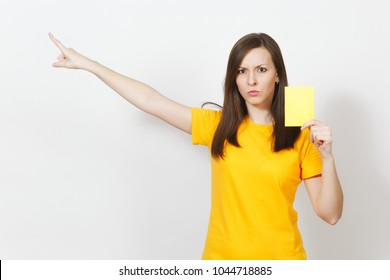 European serious severe young woman, football referee in yellow uniform show yellow soccer card, propose player retire from field isolated on white background. Sport, play, healthy lifestyle concept