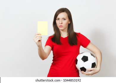 European serious severe young woman, football referee or player in red uniform showing yellow card, holding soccer ball isolated on white background. Sport play football, healthy lifestyle concept