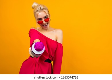 European sexy girl singer in a bright red dress with bare shoulders with a microphone in her hands on a yellow background