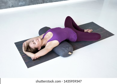 European slim woman practicing yoga lying in Reclined Butterfly exercise relaxing after practice