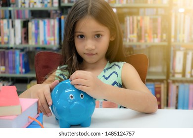 European small schoolgirl, white skin, long light brown hair. In the library are many books and nobody here. She's bringing the silver coins in the blue piggy bank, blurred model, focus foreground