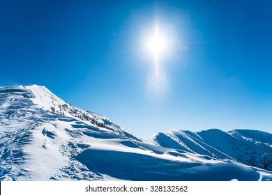 European snowy landscape with sun, Snowy ridge of mountains, Background winter mountains alps