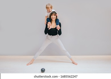 European sportive mother piggybacking her toddler baby son in fitness clothing at home on gray background. Lounge exercise. Motherhood, healthy lifestyle concept.