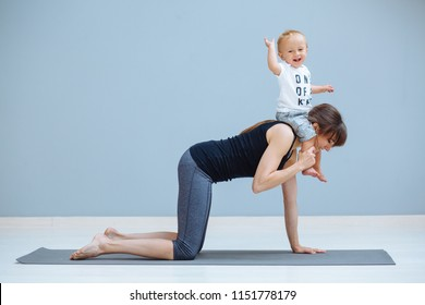European sporty mother practicing gymnastics doing exercises standing on all fours while her little son sitting on his mother's shoulders at simple home interior. Motherhood, healthy lifestyle concept