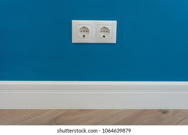 European standard 220 volt wall electrical outlet on wall with baseboard and hardwood floor