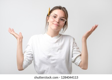 European student woman in gesture of asking over gray background.