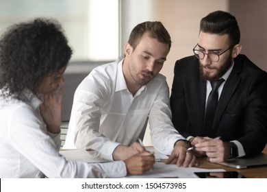 European team leader lead corporate meeting seated at desk with arabian and african ethnicity diverse teammates businesspeople working together strategizing reviewing document analyzing financial data