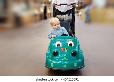 European toddler boy sitting in the shopping cart made as toy car