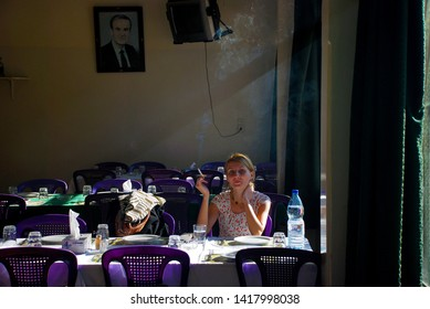 European tourist lunches at a local restaurant. She smokes a cigarette, and behind it is a portrait of Hafez Assad. Syria before the war. Maaloula, Syria, Middle East. November 23, 2007.