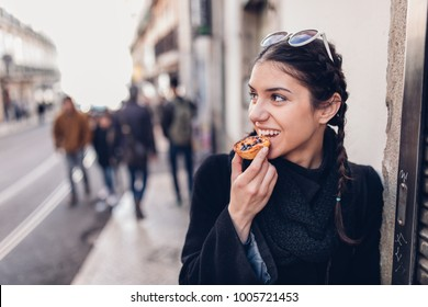 European tourist woman trying out local food.Eating traditional Portuguese egg custard tart pastry dessert pastel de Nata.