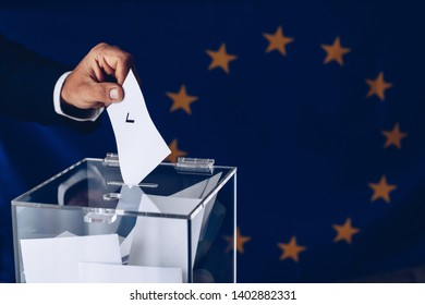 European Union elections. Man inserting his vote to ballot box.