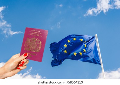 European Union (EU) flag against a blue sky with digital composite of woman holding a UK passport - UK is set to leave the EU in 2019