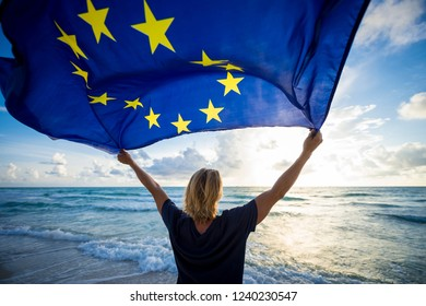 European Union flag flying in bright morning sunlight held up by man with blond hair standing on empty Mediterranean beach