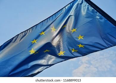European union flag ob blue sky and sun background