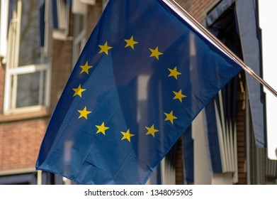 European union flag waving in the wind with a building in the background