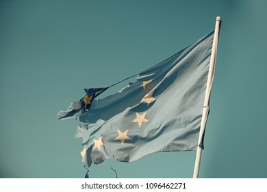 European union twelve star flag torn and with knots in wind on blue sky background. Flag is torn off at side, symbol of problems, decay, disintegration, decomposition, breakdown.