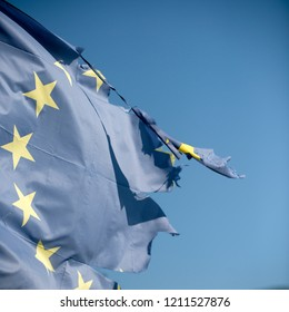 European union twelve star flag torn and with knots in wind on blue sky background, close up. Flag is torn off at side, symbol of problems, decay, disintegration, decomposition, breakdown