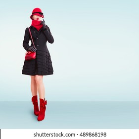 European winter style woman isolated on light blue background. Wearing a black wool coat, red hat, scarf,purse,gloves and boots.