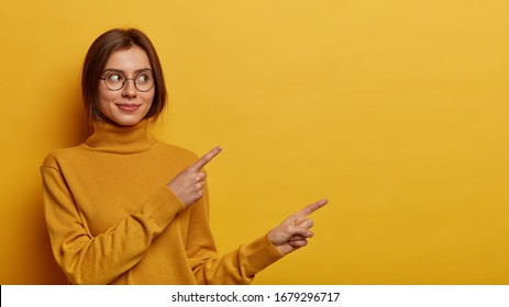European woman with appealing appearance points fingers right, shows discount offer or banner, suggests visit link or webpage, wears turtleneck, isolated on yellow wall, gives recommendation.