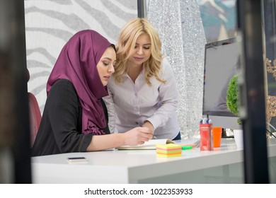 European woman and asian muslim woman working together on same project