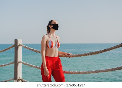 European woman in a bikini top and red pants wearing protective face mask at the public beach. New normal during coronavirus outbreak. Covid 19 pandemic rules