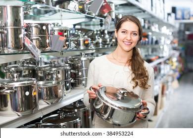 european woman buying pan in shop cookware