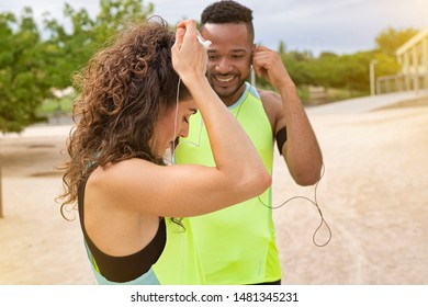 European woman with curly hair placing her helmets on her ears to start her career session is accompanied by a young black African American who looks out of focus in the background in the image