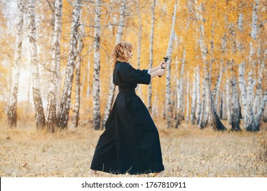 European woman with a katana in a kimono. the girl trains martial arts. a woman in the autumn forest. a warrior with a cold weapon in his hands