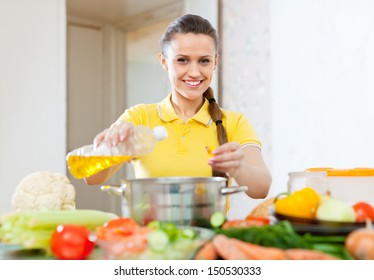 European woman  pouring oil from bottle into pan