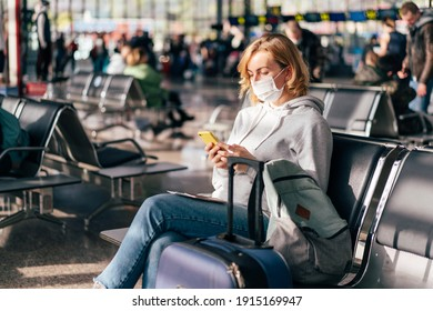 A European woman in a protective medical mask on her face sits at the airport waiting for a flight and uses the phone. - Shutterstock ID 1915169947