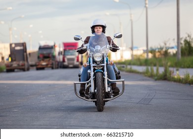 European woman riding chopper motorcycle on asphalt highway, front view