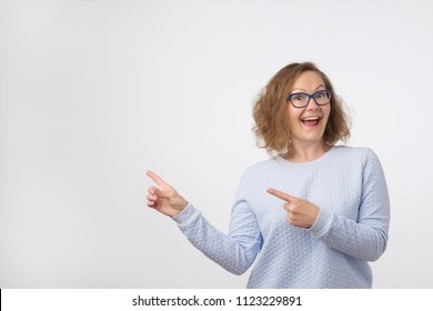 European woman swith smile showing product. Beautiful girl with curly hair pointing to the side . Presenting your product. Positive facial emotion or body language concept