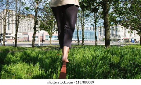 European woman is walking along a tight line in a city park. Girl balances on the slackline from the back