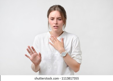 European woman in white t-shirt having a sore throat. Lost a voice. Problem with health. She isshocked with news.